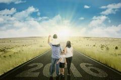Famiglia che cammina sulla strada con i numeri 2016 Fotografie Stock
