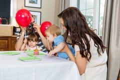 Famiglia che celebra il compleanno del figlio a casa Fotografia Stock