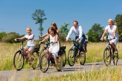 Famiglia che cicla all'aperto di estate Immagini Stock