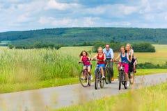 Famiglia che cicla di estate nel paesaggio rurale Immagine Stock