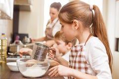 Famiglia che cucina fondo Bambini nella cucina Fotografia Stock