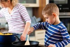 Famiglia che cucina nella cucina fotografie stock