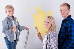 Famiglia che dipinge una parete Fotografie Stock Libere da Diritti
