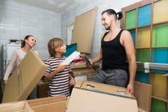 Famiglia che disimballa le scatole con nuova mobilia Immagini Stock