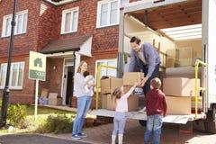 Famiglia che disimballa muoversi in scatole dal camion di rimozione immagine stock libera da diritti