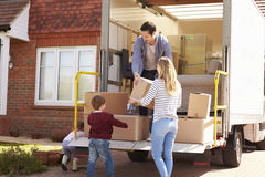 Famiglia che disimballa muoversi in scatole dal camion di rimozione fotografia stock libera da diritti