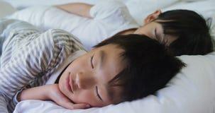 Famiglia che dorme insieme sul letto in camera da letto 4k video d archivio