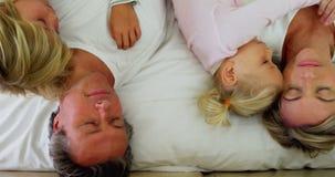 Famiglia che dorme sul letto nella sala 4k del letto archivi video