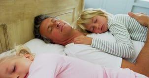 Famiglia che dorme sul letto nella sala 4k del letto stock footage