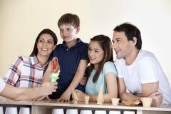 Famiglia che esamina cameriere Giving Ice Cream il contatore fotografia stock libera da diritti