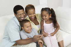 Famiglia che esamina immagine sul telefono della macchina fotografica Fotografia Stock Libera da Diritti