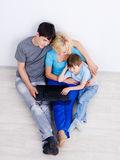Famiglia che esamina insieme computer portatile Fotografia Stock