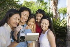 Famiglia che esamina lo schermo della videocamera nella vista frontale del cortile posteriore Immagine Stock