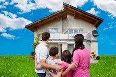 Famiglia che esamina nuova casa sul campo erboso immagini stock libere da diritti