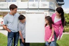 Famiglia che esamina una scheda vuota fuori della casa Immagine Stock Libera da Diritti