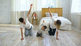Famiglia che fa gli esercizi relativi alla ginnastica nell'istruzione sana di vita della camera da letto a casa - fotografie stock