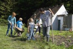 Famiglia che fa il giardinaggio fuori del cottage Fotografie Stock