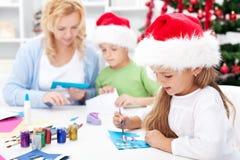 Famiglia che fa insieme le cartoline d'auguri stagionali Fotografie Stock