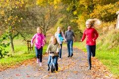 Famiglia che fa passeggiata nella foresta di caduta di autunno Fotografie Stock