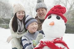 Famiglia che fa pupazzo di neve in un parco nell'inverno immagine stock libera da diritti