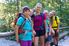 Famiglia che fa un'escursione nella foresta che sta su poco ponte Immagini Stock