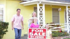 Famiglia che fa una pausa per il segno di vendita fuori della casa archivi video