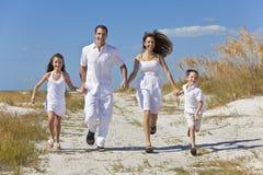 Famiglia che funziona avendo divertimento alla spiaggia Fotografia Stock Libera da Diritti