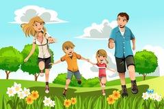 Famiglia che funziona nella sosta Fotografia Stock