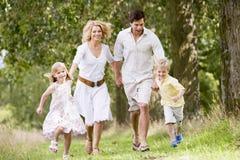 Famiglia che funziona sul sorridere delle mani della holding del percorso Immagine Stock