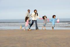 Famiglia che funziona sulla spiaggia di inverno Fotografia Stock