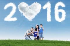 Famiglia che gioca bolla al campo con i numeri 2016 Immagini Stock