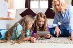 Famiglia che gioca con il calcolatore del ridurre in pani nel paese Fotografie Stock