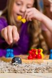Famiglia che gioca gioco da tavolo a casa Fotografia Stock