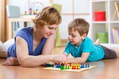 Famiglia che gioca gioco da tavolo a casa sul pavimento a casa Fotografie Stock Libere da Diritti