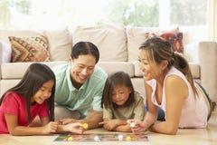 Famiglia che gioca gioco da tavolo nel paese Immagini Stock Libere da Diritti