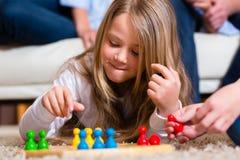 Famiglia che gioca gioco da tavolo nel paese Fotografia Stock Libera da Diritti