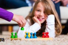Famiglia che gioca gioco da tavolo nel paese Fotografia Stock