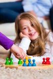 Famiglia che gioca gioco da tavolo nel paese Immagini Stock