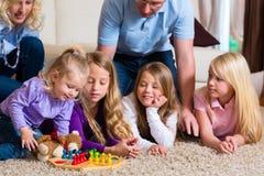 Famiglia che gioca gioco da tavolo nel paese Fotografie Stock Libere da Diritti