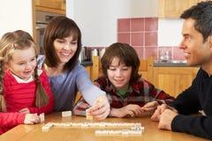 Famiglia che gioca i domino in cucina Fotografie Stock Libere da Diritti