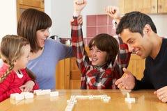 Famiglia che gioca i domino in cucina Fotografia Stock Libera da Diritti