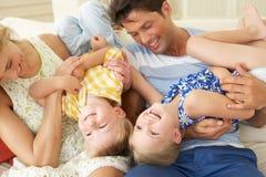 Famiglia che gioca sul sofà nel paese Fotografie Stock