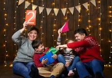 Famiglia che giocano con il testo del nuovo anno, sedendosi sul fondo di legno scuro con le luci e le bandiere di natale e divert fotografia stock