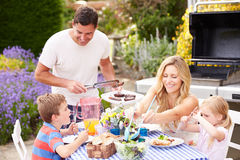 Famiglia che gode del barbecue all'aperto in giardino Fotografia Stock
