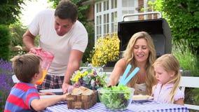 Famiglia che gode del barbecue all'aperto in giardino stock footage