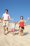 Famiglia che gode della festa della spiaggia che funziona giù la duna Fotografie Stock