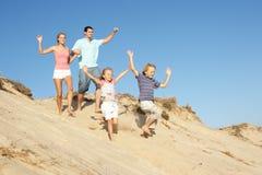 Famiglia che gode della festa della spiaggia che funziona giù la duna Fotografia Stock