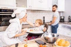 Famiglia che gode della mattina in cucina fotografie stock libere da diritti