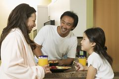 Famiglia che gode della prima colazione in cucina fotografie stock libere da diritti