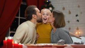 Famiglia che guarda alla macchina fotografica che bacia figlia sveglia, vigilia di natale, effetto d'annata della foto video d archivio